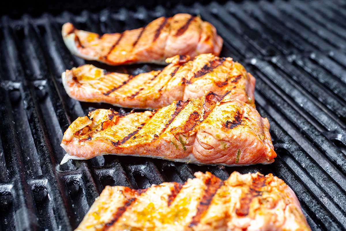 Grilled Salmon Fillet with Mango Salsa - salmon fillets on a grill skin side down