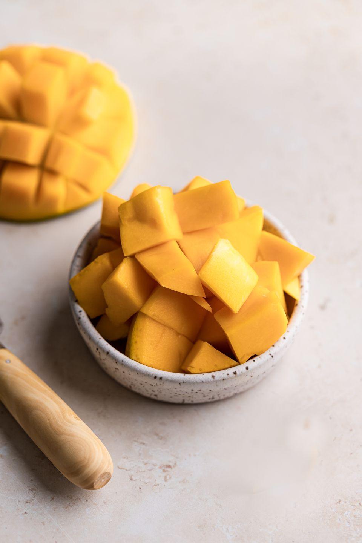 A bowl of ripe mango chopped into cubes.