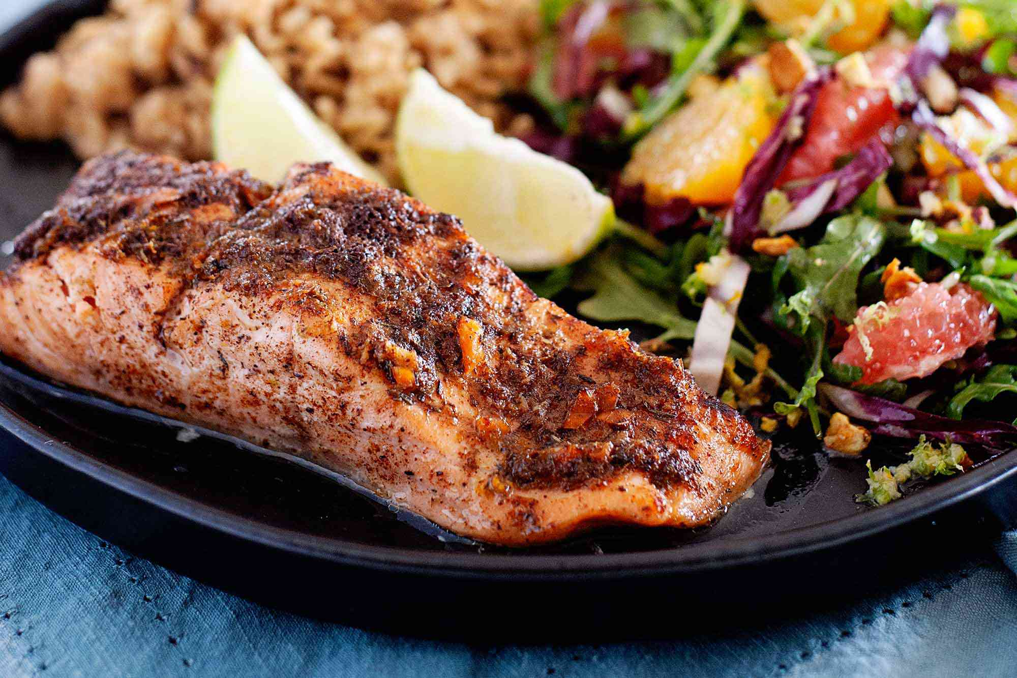 Side view of a fillet of broiled jerk salmon. The salmon has juices pooled at the bottom of it. A mixed green salad with citrus, two lime wedges and rice are visible on the plate behind the salmon. The plate is on a blue linen.