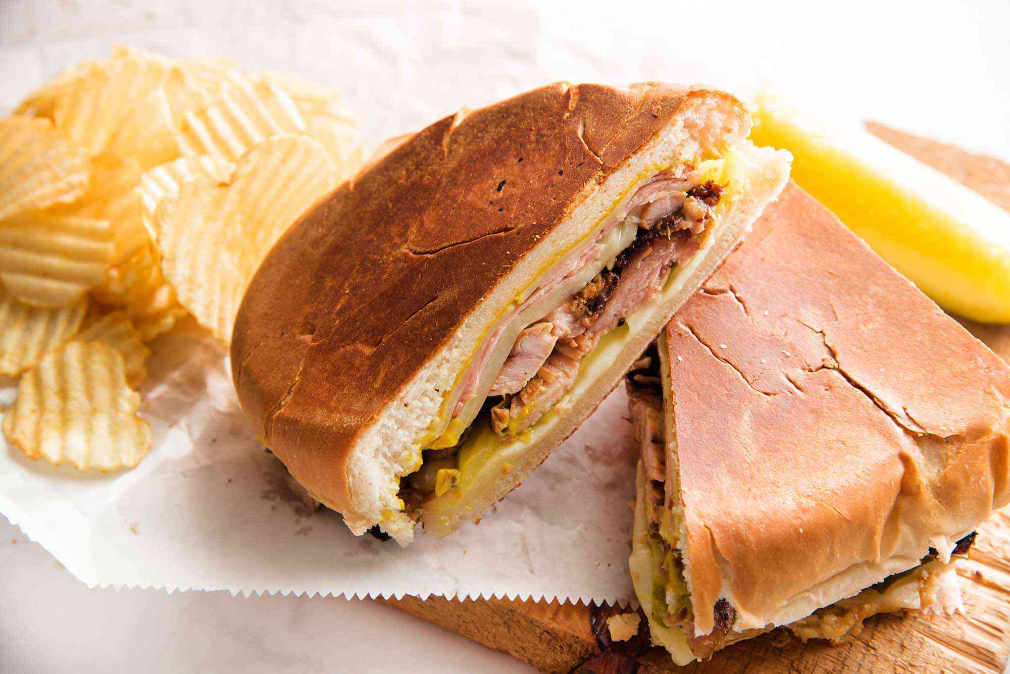 Two halves of a traditional cuban sandwich are resting on parchment paper and a wooden cutting board. Ridged potato chips and a pickle are in the background.