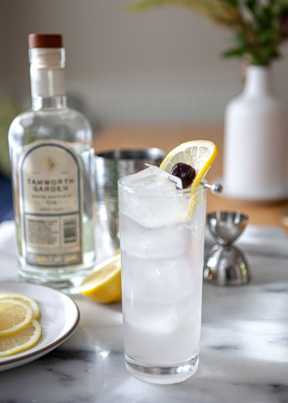 Tom Collins cocktail garnished with lemon and on a table with a bottle of gin.