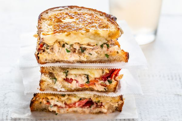 Grilled tuna sandwich cut in half and stacked on top of each other. The bread is toasted and tuna, melted cheese and tomatoes are visible in the filling.