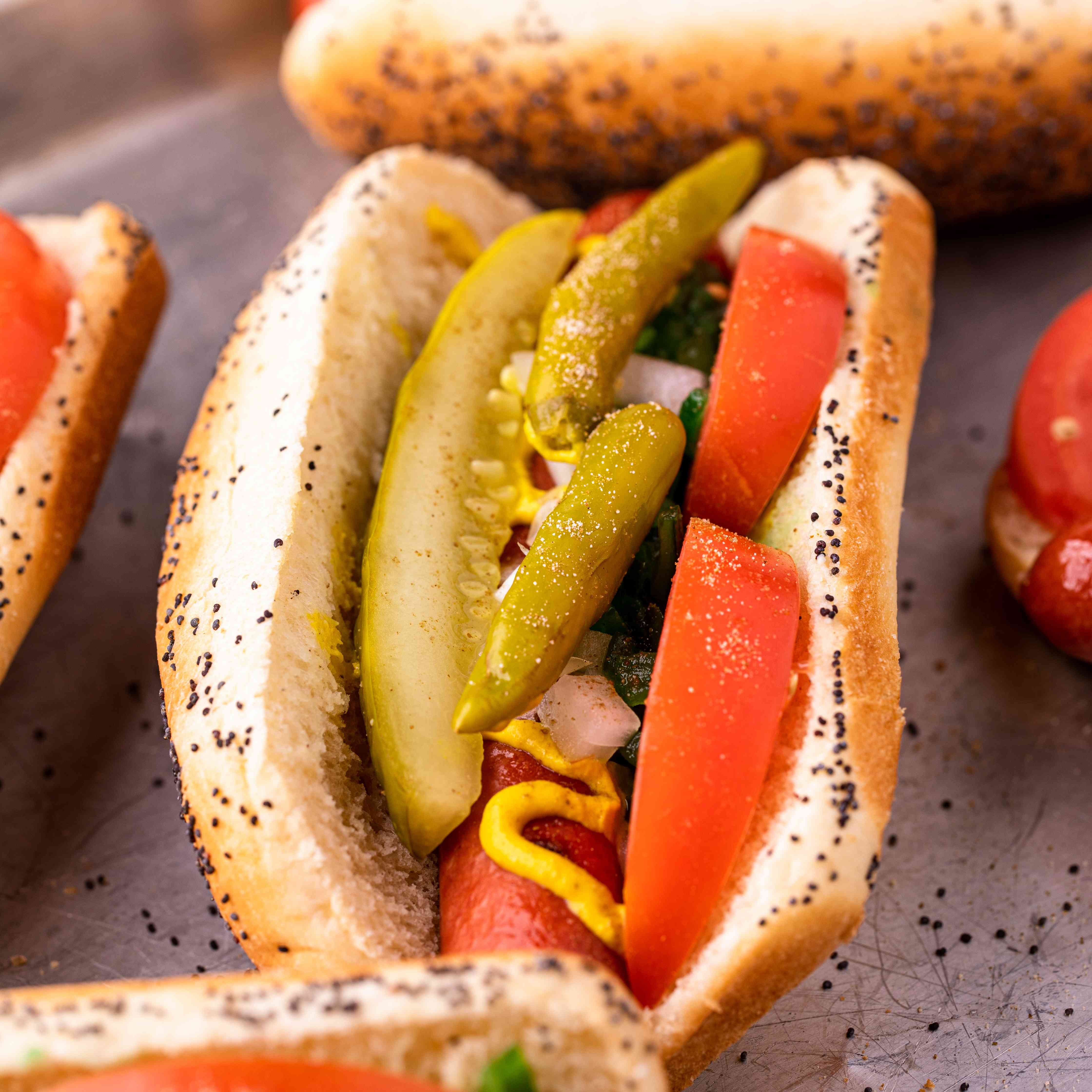 Chicago dogs with tomato and pickles on a pan.