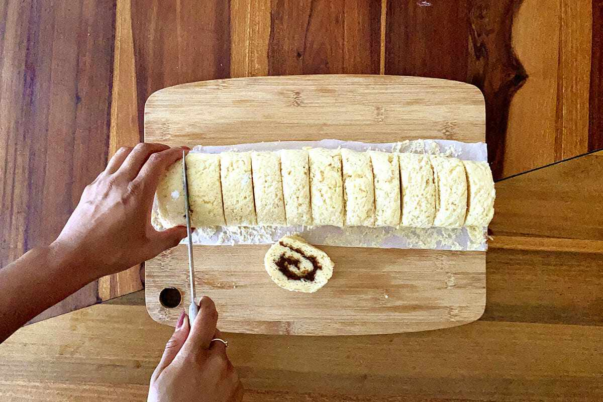Rolls being sliced on a cutting board to show how to make gluten free cinnamon rolls.