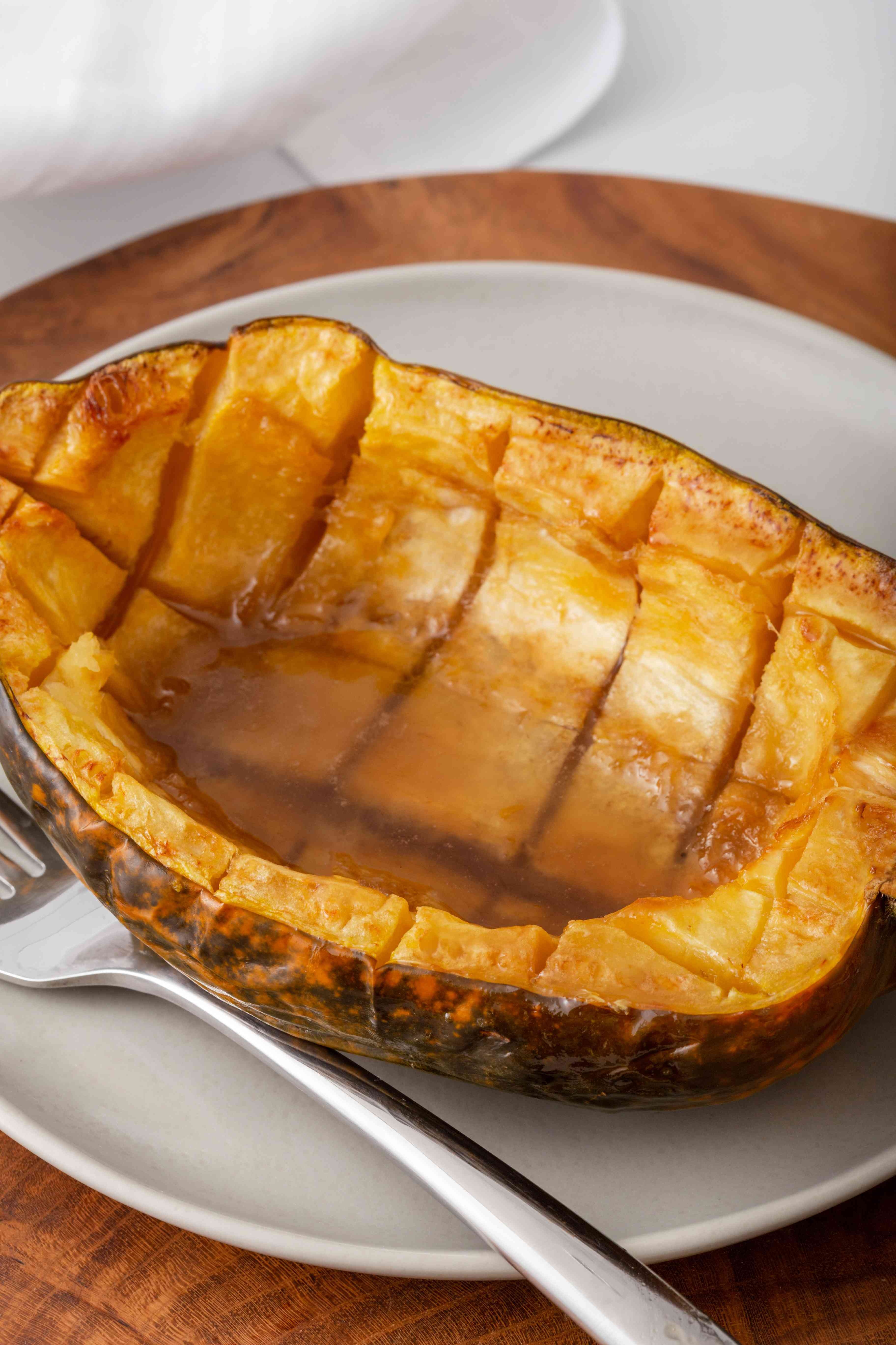 Side view of roasted acorn squash on a plate.