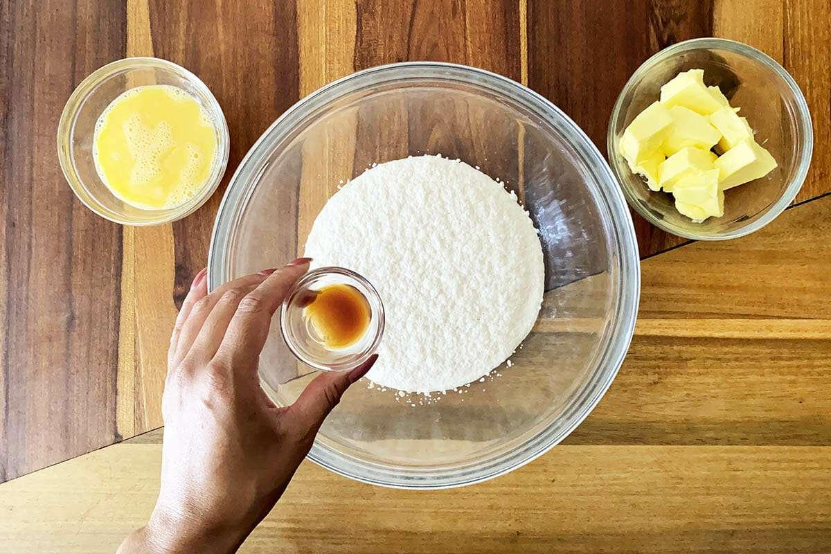 Adding vanilla to ingredients for easy gluten free cinnamon rolls.