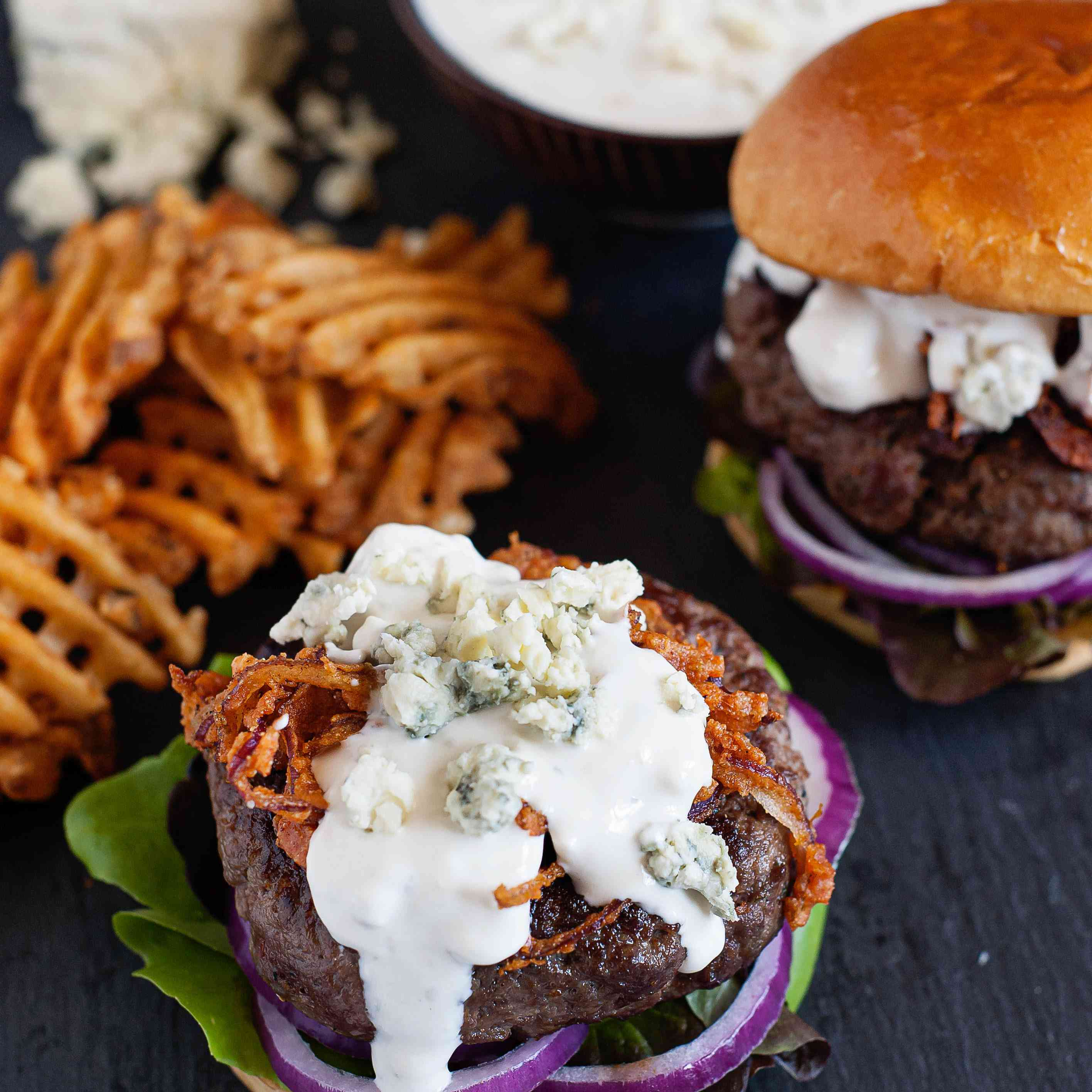 Homemade Blue Cheese Sauce - blue cheese sauce on a hamburger with fries in the background