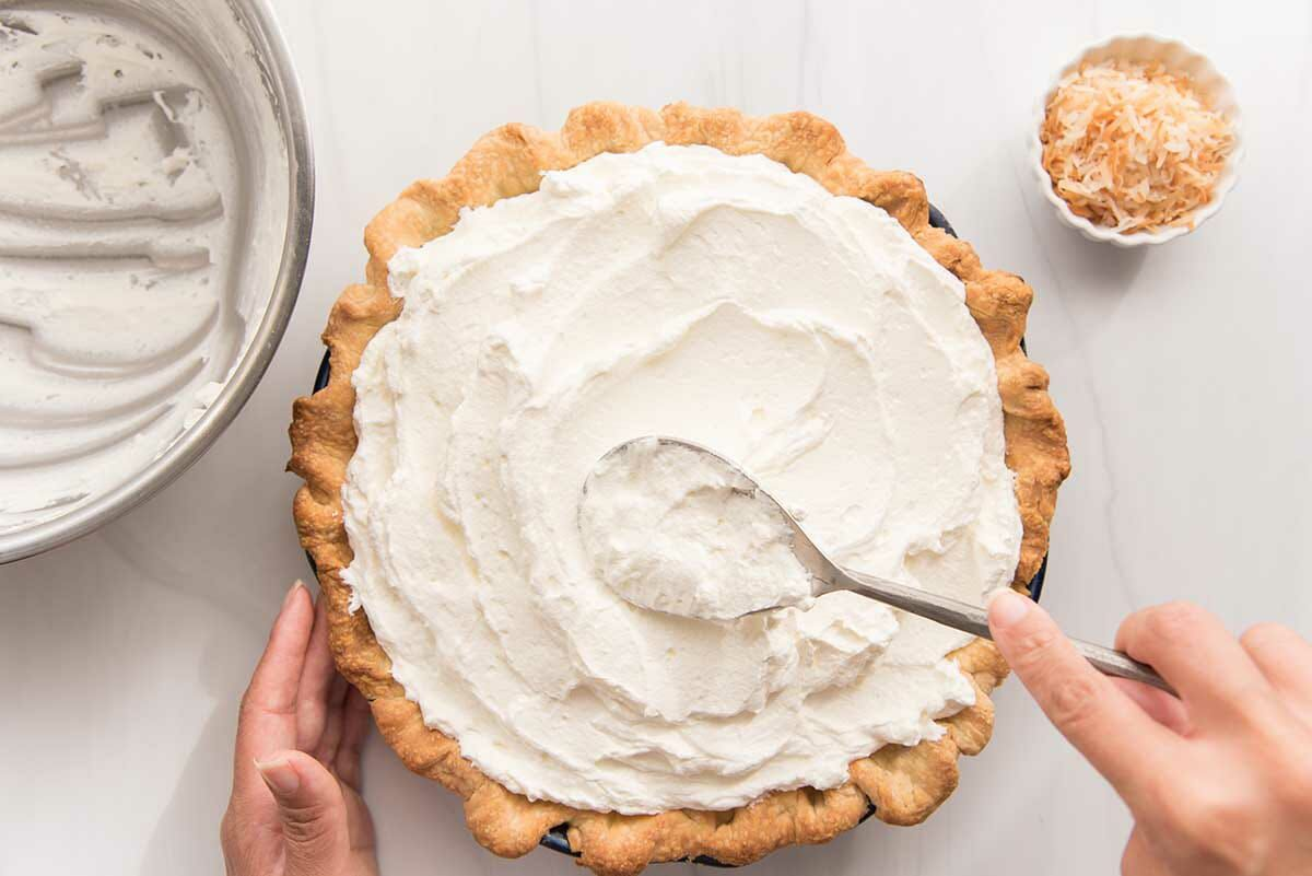 A spoon spreads whipped cream over the top of the best coconut cream pie.
