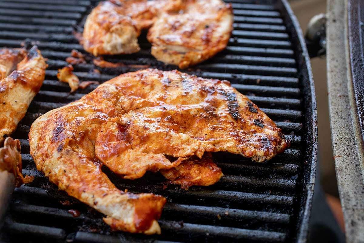 BBQ chicken on the grill to make Homemade BBQ Chicken Sandwiches.