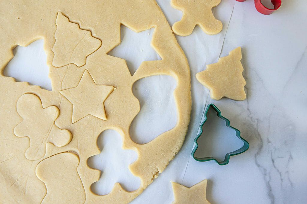 Dough for Christmas sugar cookies is rolled on a counter with shapes cut out.