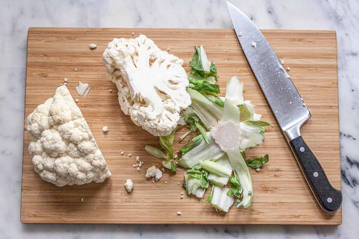 Vegan Cauliflower Sandwich Recipe - a head of cauliflower being sliced on a wooden cutting board
