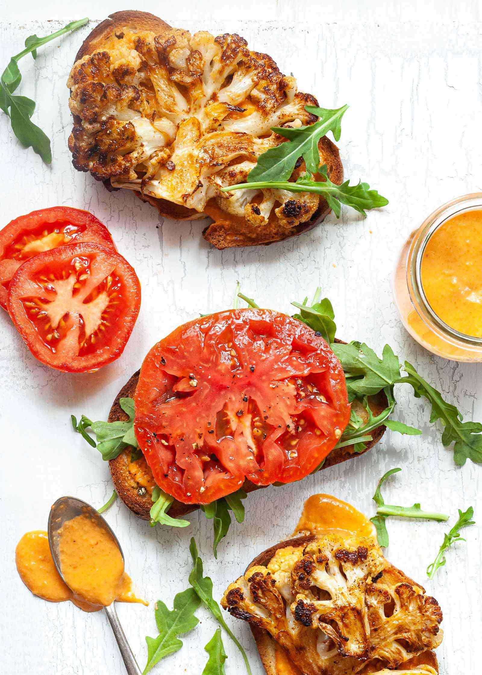 Easy Cauliflower Steak Sandwich - open faced sandwich with sliced tomatos, crusty sourdough bread and red pepper aioli