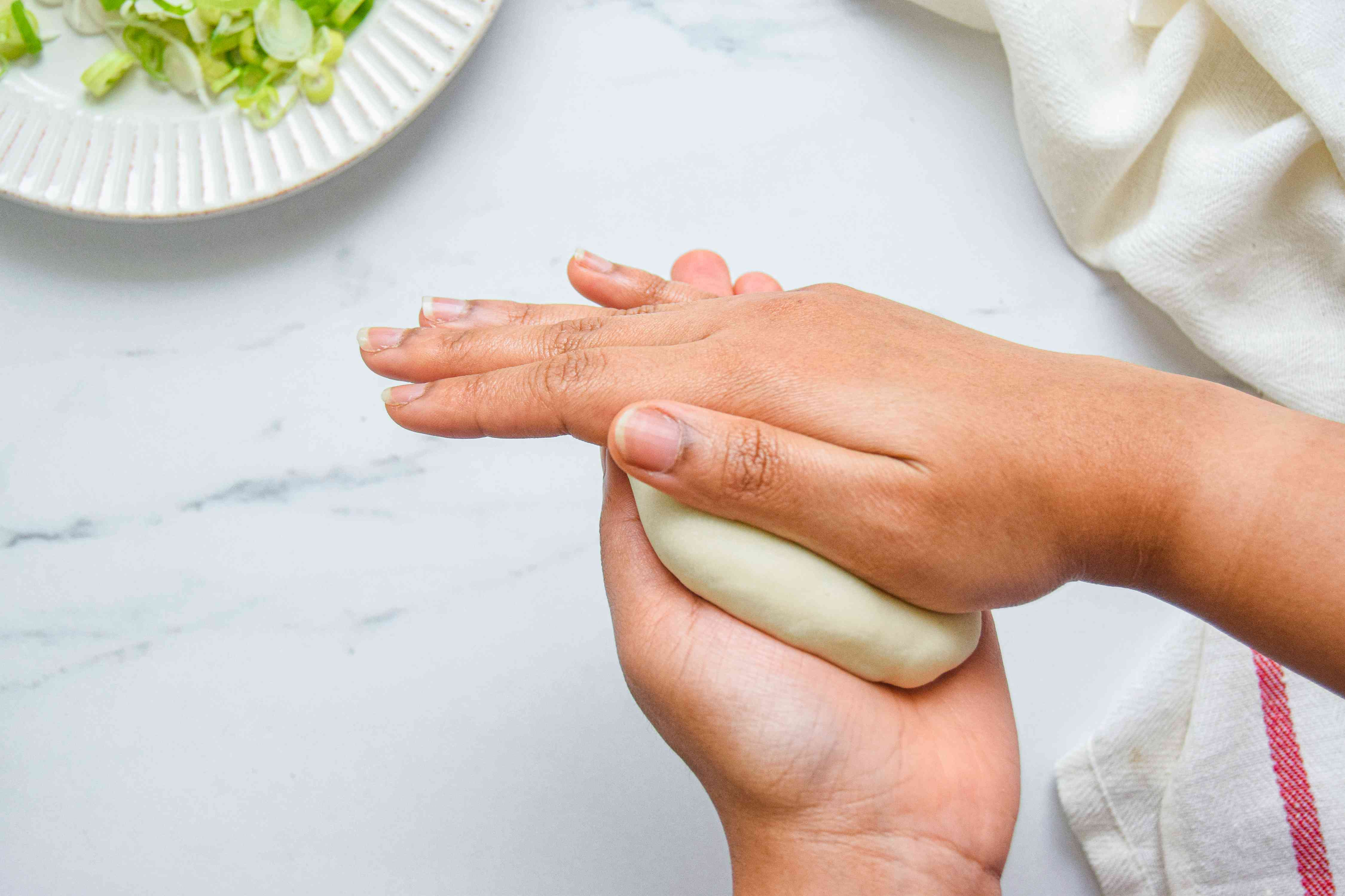 Flattening spiral scallion pancake dough in between hands.