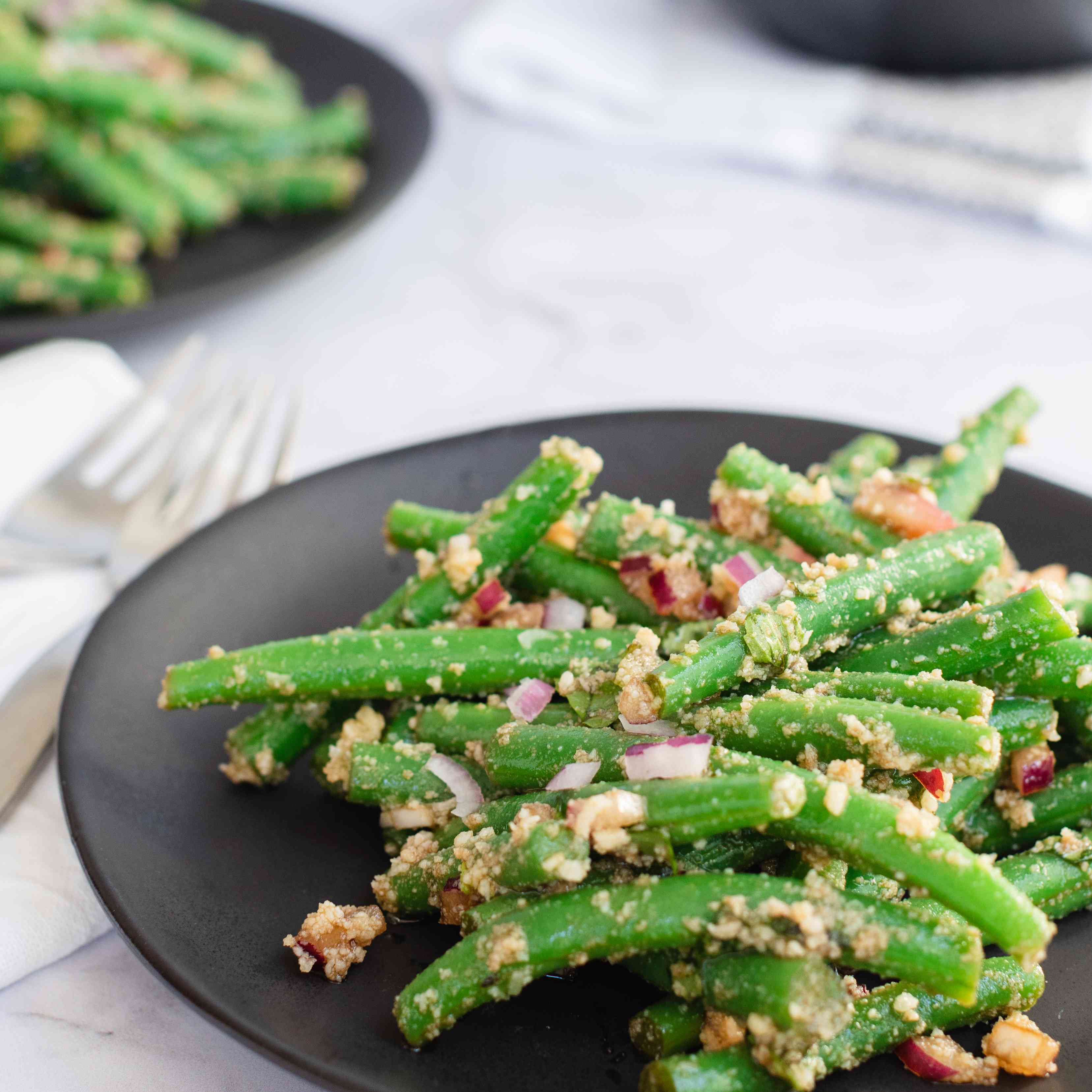Side view of three plates of green bean salad.