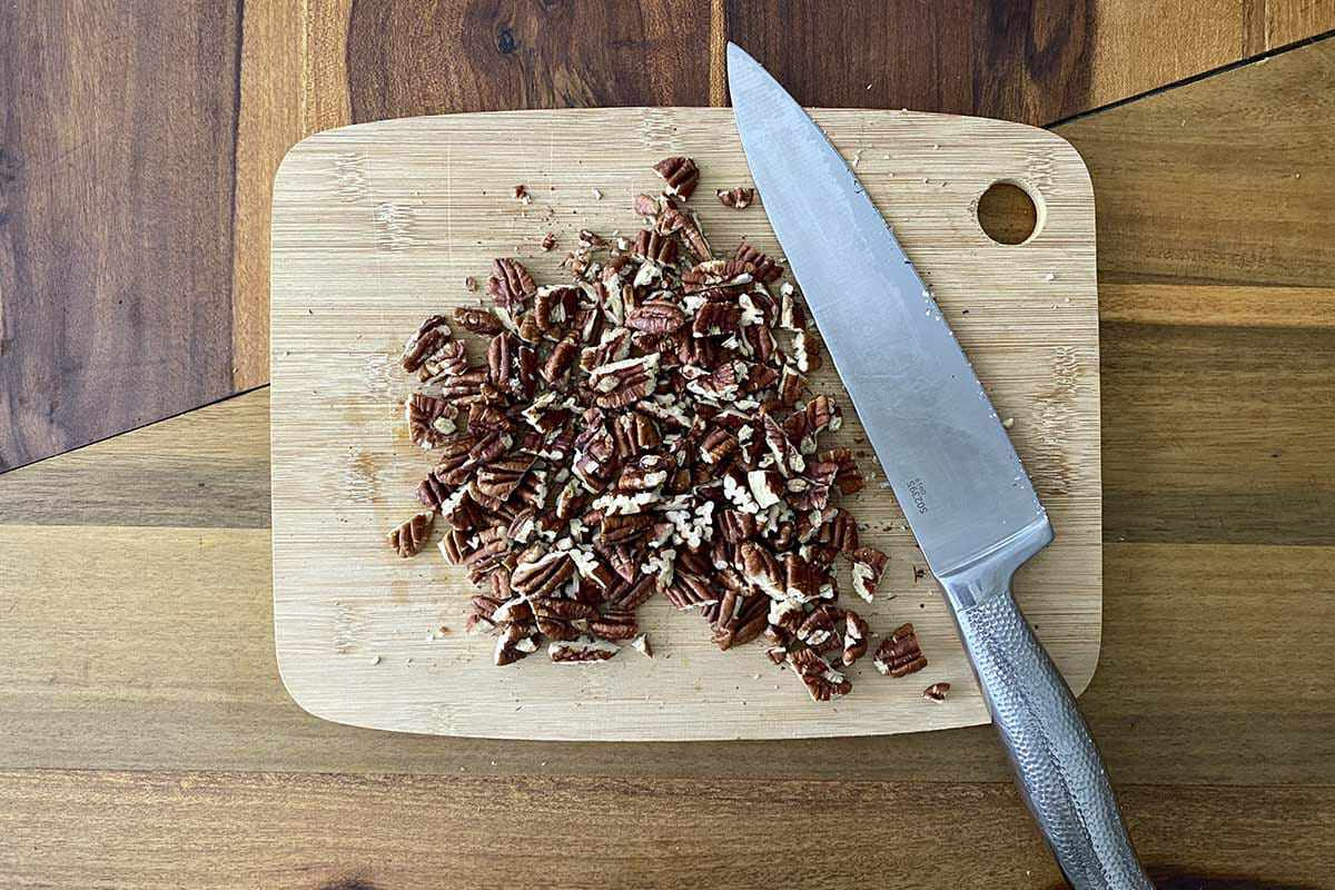 A cutting board with chopped pecans and a chef knife to make a Fall Vegetable Salad with Bacon and Maple Dijon Vinaigrette.