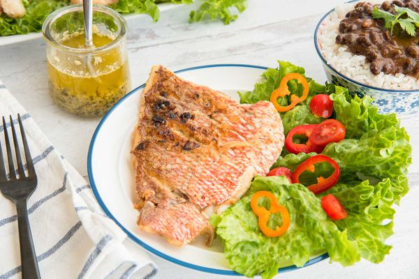 Side view of lenten fish with garlic sauce on a plate with a blue edge. A blue striped napkin and a black fork are to the left of the plate. The large fillet is crispy and pink on the outside. Lettuce and cut red and orange peppers are to the right of the snapper. A bowl of rice and black beans is to the upper right of the image. A jar with a spoon inside has chillo al Ajuillo inside. Behind is a platte with more lettuce and snapper.