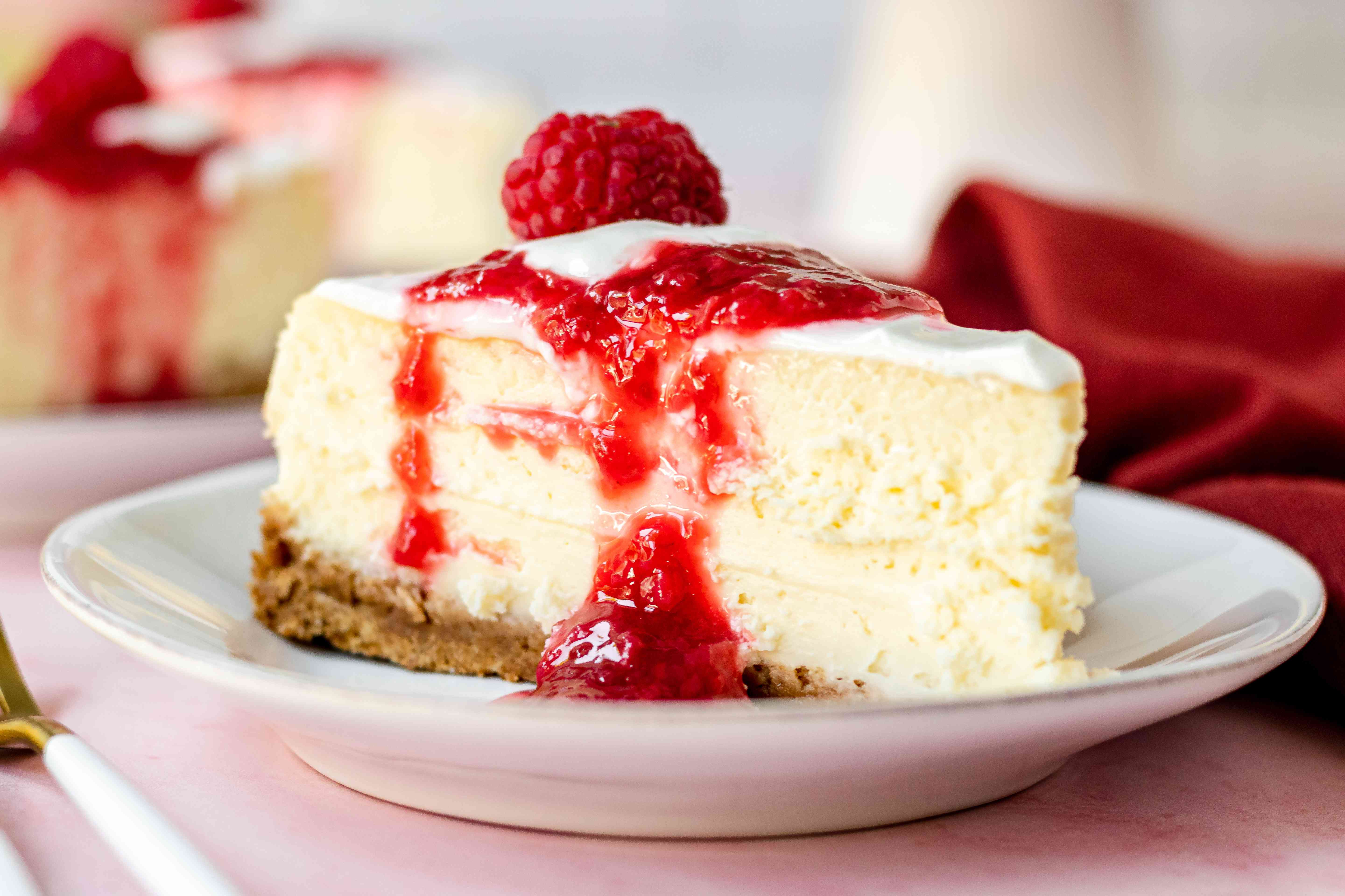 Side view of a slice of cheesecake topped with raspberry sauce.
