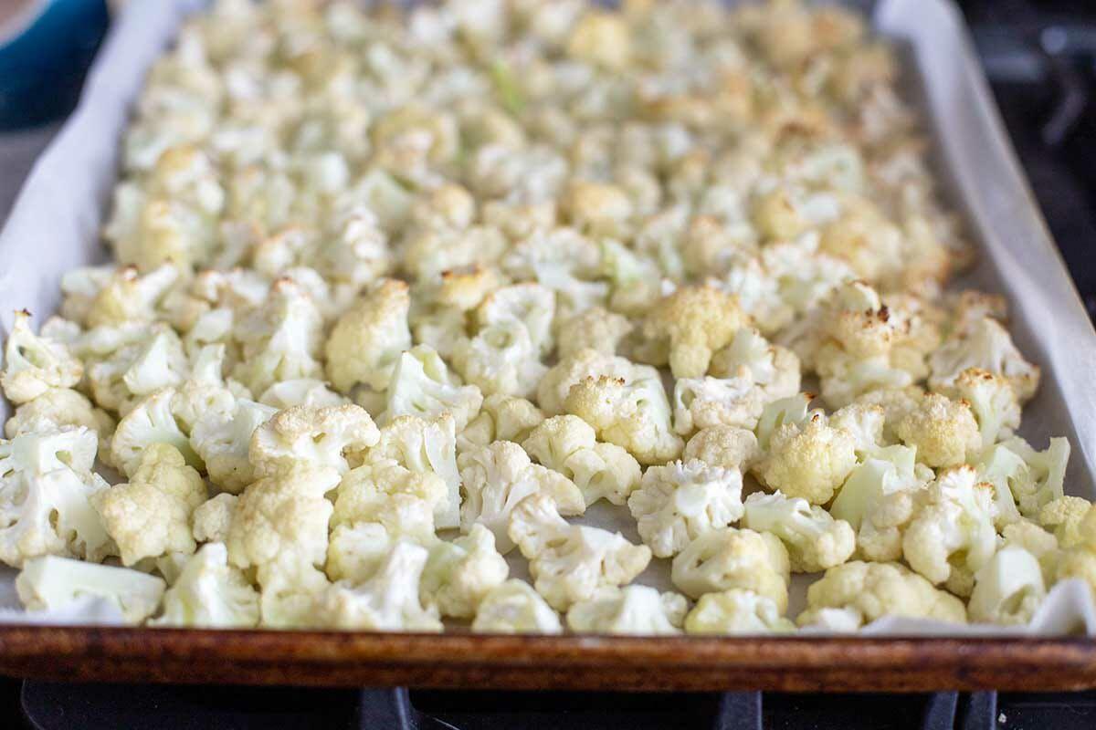 Chopped cauliflower slightly roasted in a baking sheet to make Vegetarian Cauliflower Casserole.