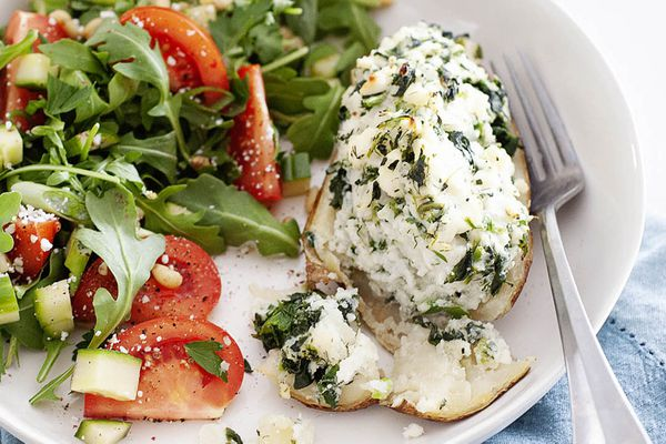 Spanakopita twice baked potatoe sliced open with a fork on a white plate with an arugula and tomato salad.