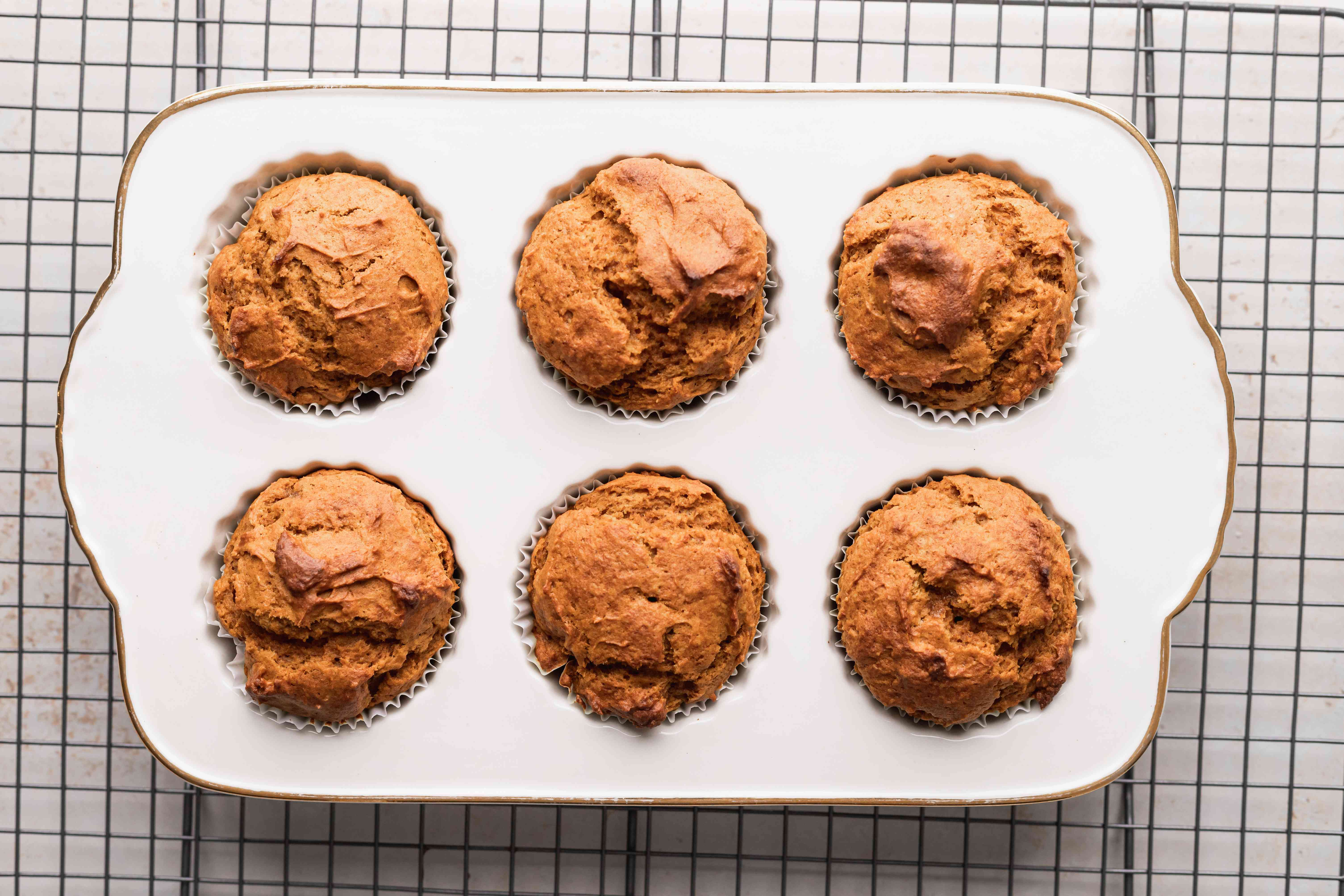 Quick and easy pumpkin muffins cooling on a rack.
