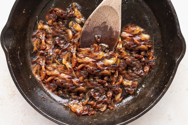 A wooden spoon stirring caramelized onions in a cast iron skillet to show how to make caramelized onions.