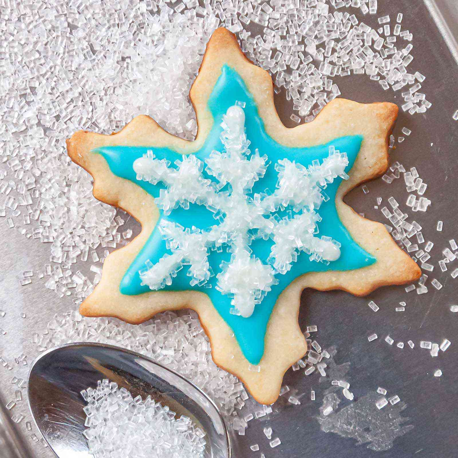Sparkling sugar spooned over a snowflake cookie decorated with Easy Royal Icing Recipe.
