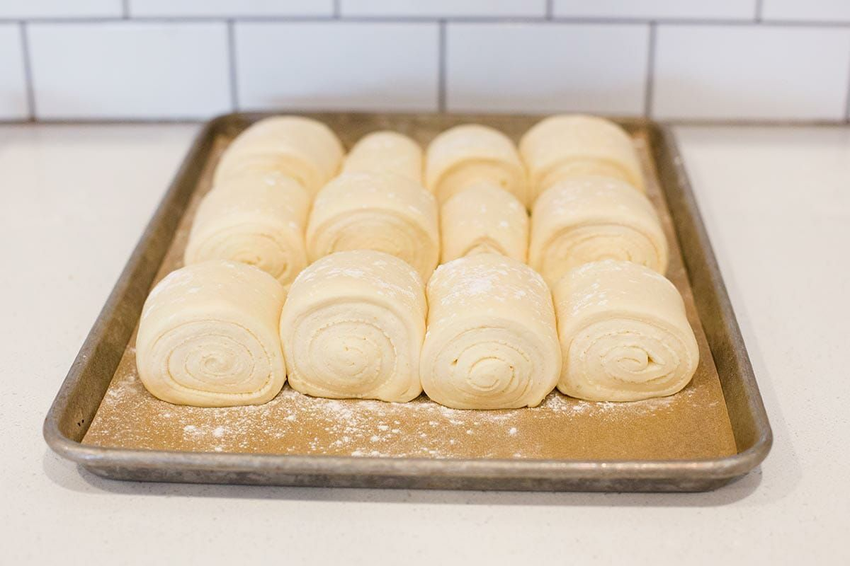 Formed lion house roll recipe set on a baking sheet and rising.