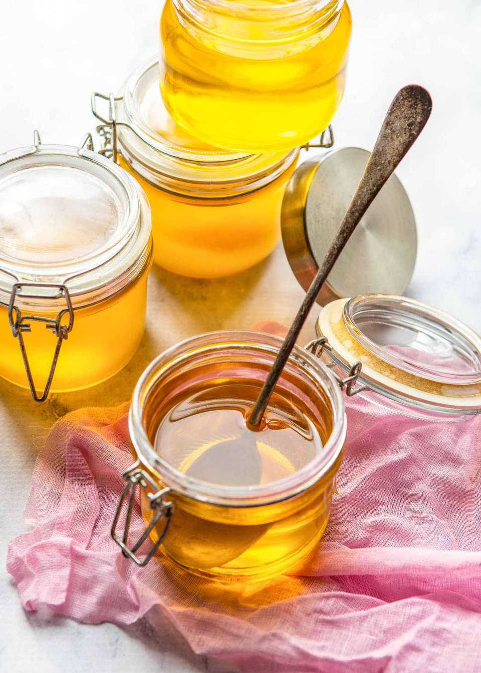Ghee butter - multiple jars of ghee on a pink cloth