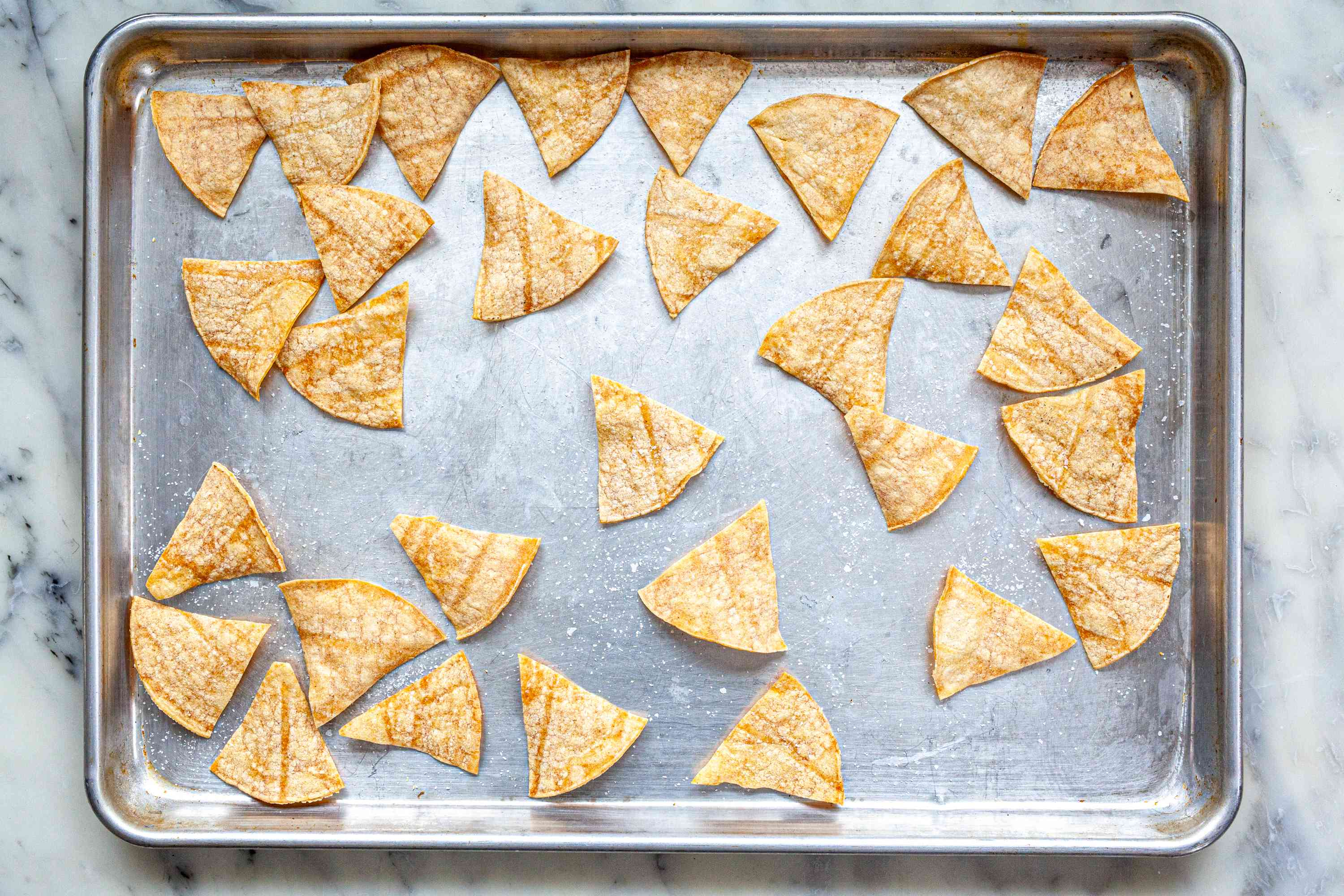 A sheet pan with crispy tortilla chips on it.