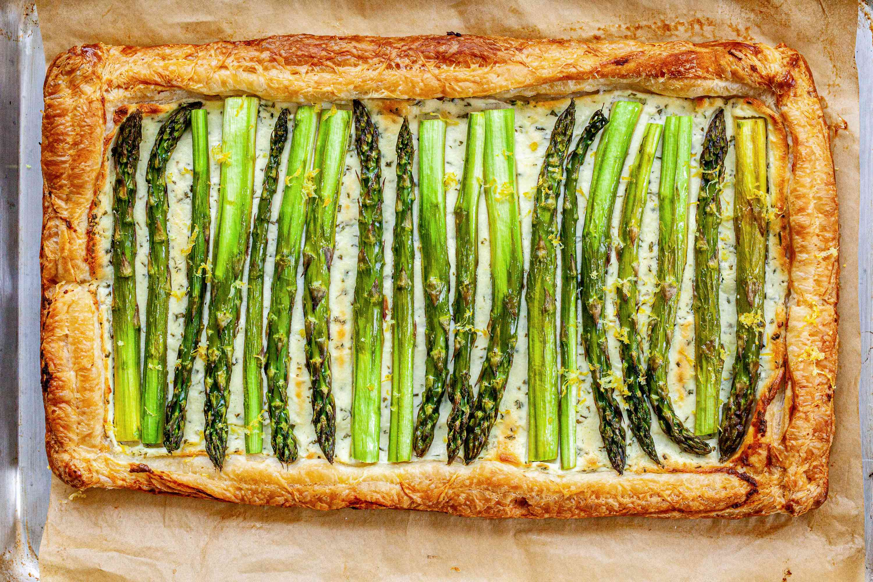 Asparagus Tart with Goat Cheese and Lemon baked and on a piece of parchment paper.