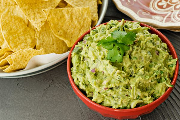 Guacamole Dip - guacamole in a bowl wtih chips on the side