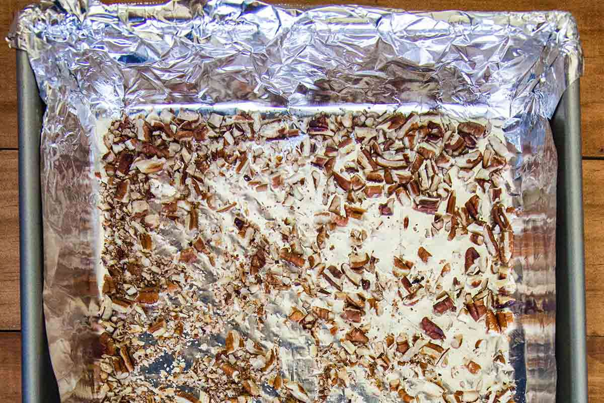 Chopped pecans on a foil covered baking sheet to make a Toffee Recipe.