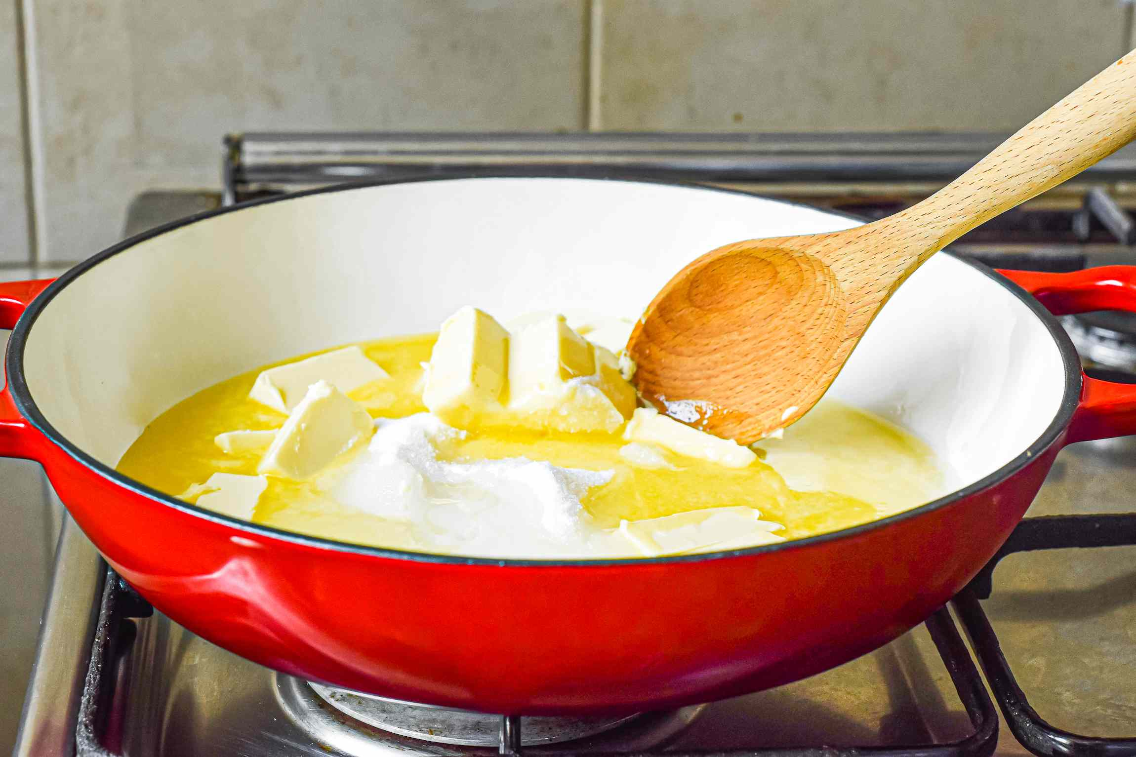 Melting butter in a red pan to make almond roca recipe.