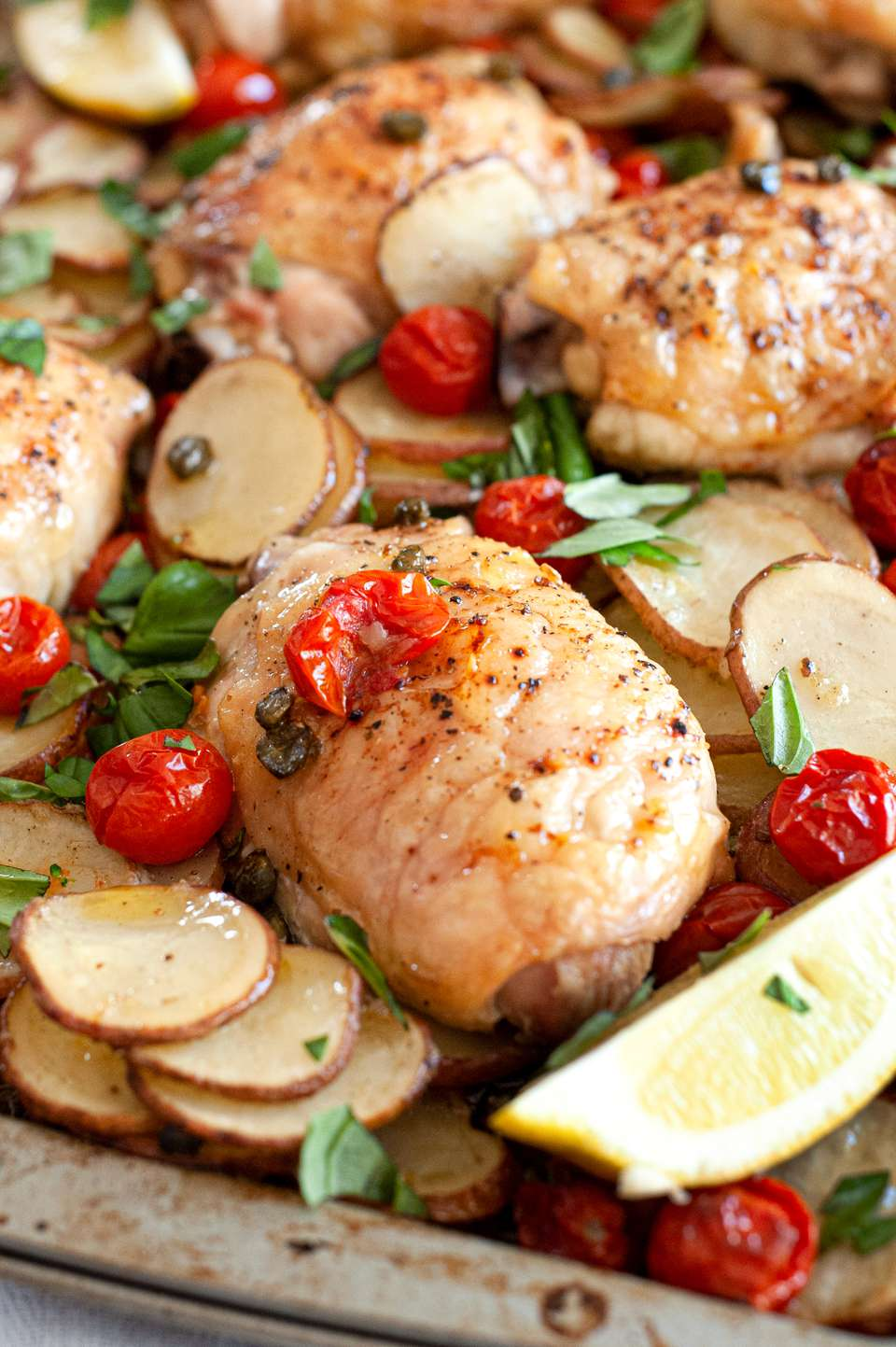 Sheet pan chicken thighs with tomatoes, potatoes, capers, and basil on a sheet pan.