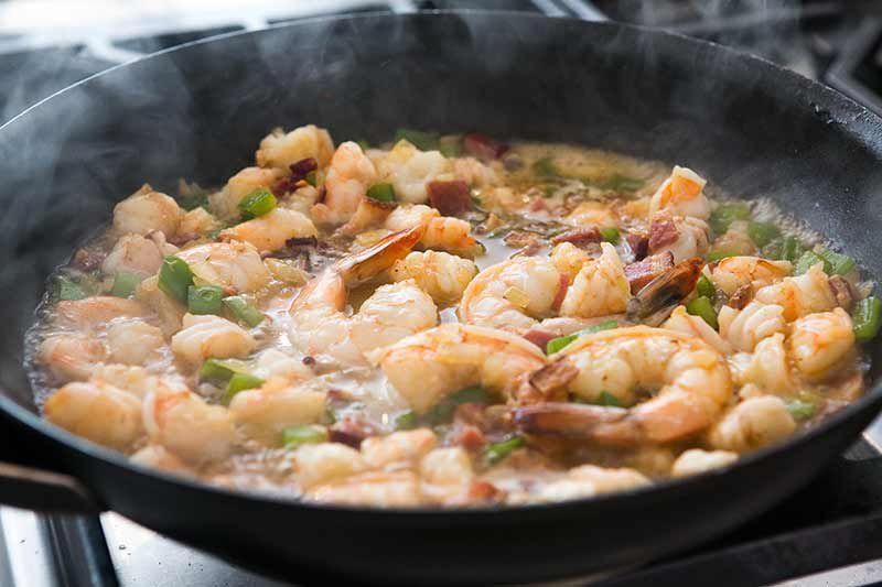 adding stock to shrimp in pan