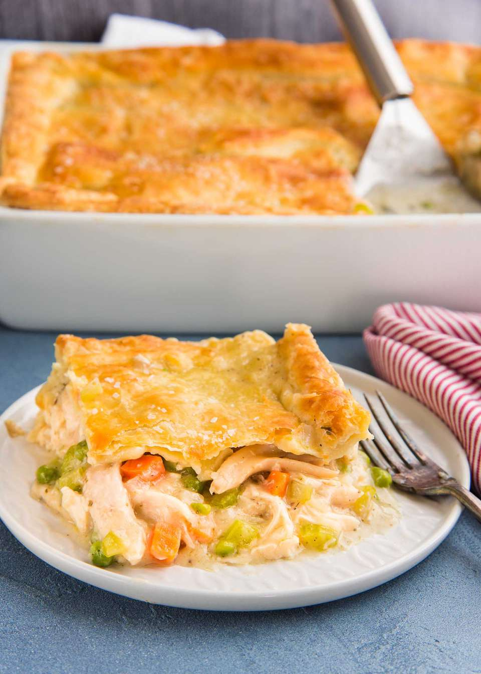 A slice of homemade Chicken Pot Pie is on a white plate and the rest of the casserole is behind it.
