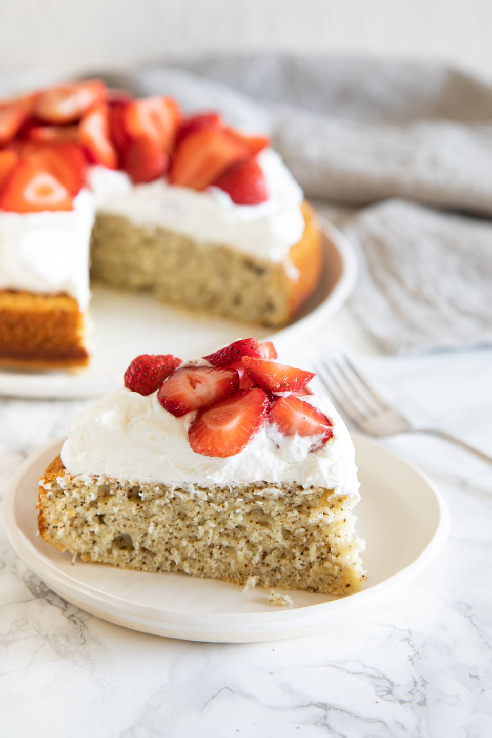A slice of The BEST Earl Grey Yogurt Cake on a plate and topped with whipped cream and strawberries. The rest of the cake is set behind the plate.