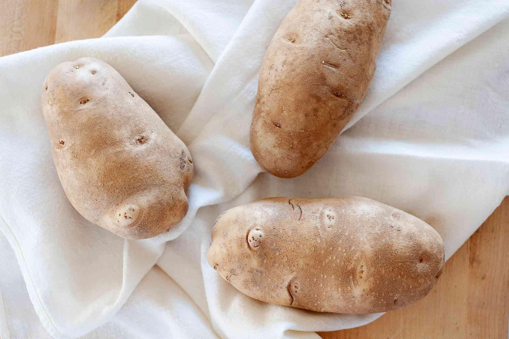Three russett potatoes on a white linen.