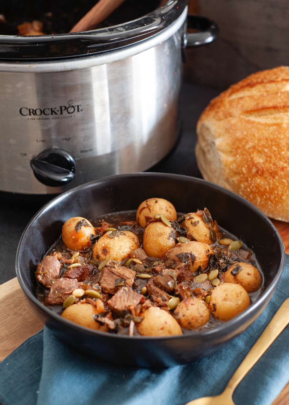 Slow Cooker Lamb Stew in a bowl with a slow cooker set behind it.