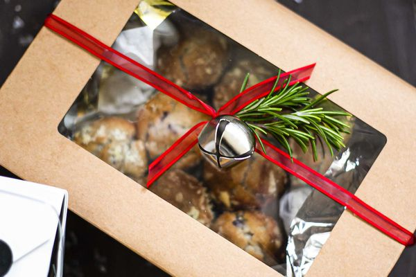 Muffins packed in a paper box with a red ribbon and bell