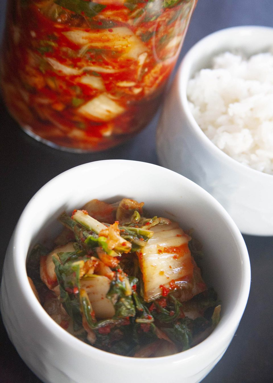 A bowl of easy homemade kimchi set by a bowl of rice and with the jar of kimchi behind it.