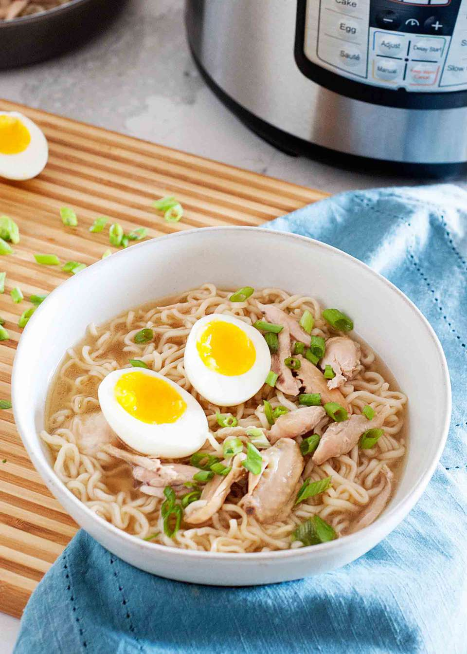 A bowl of Pressure Cooker Chicken Wing Ramen with an Instant Pot in the background