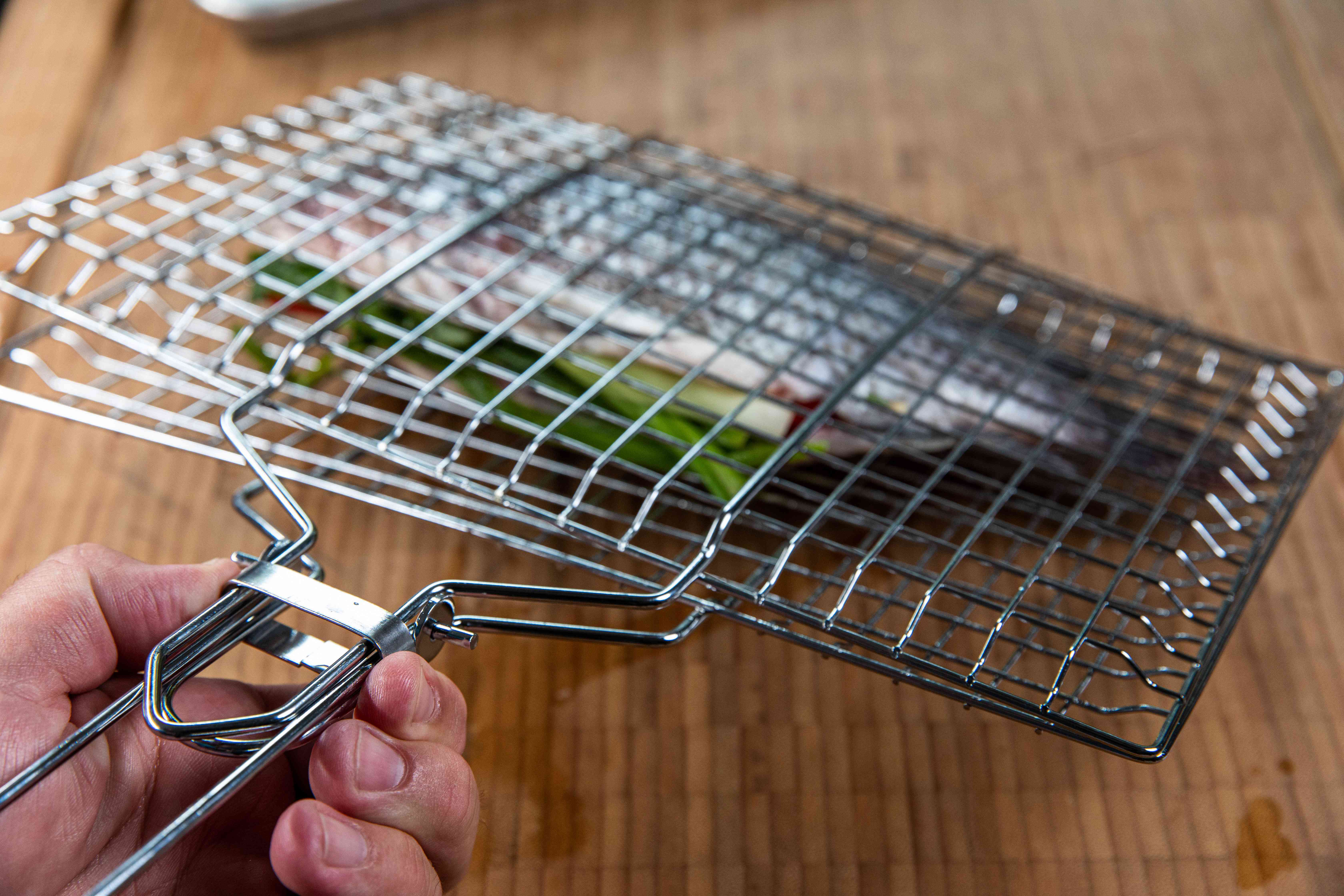 A grill cage with a whole tilapia inside.