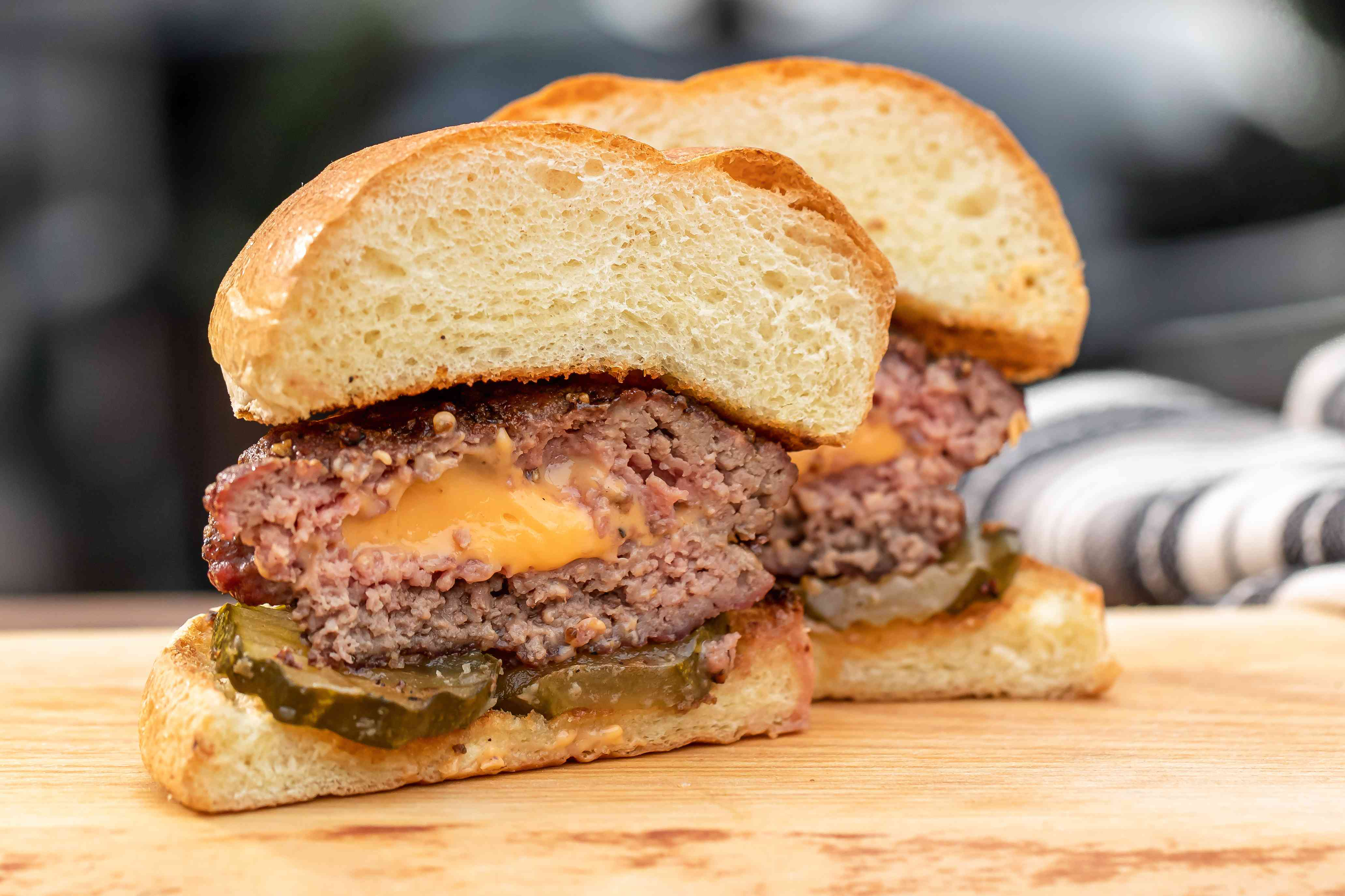 Side view of a Jucy lucy burger cut in half to show the cheese in the middle and on a wooden cutting board.