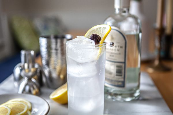 Classic Tom Collins cocktail garnished with lemon with a plate of lemons to the left and a bottle of gin behind it.