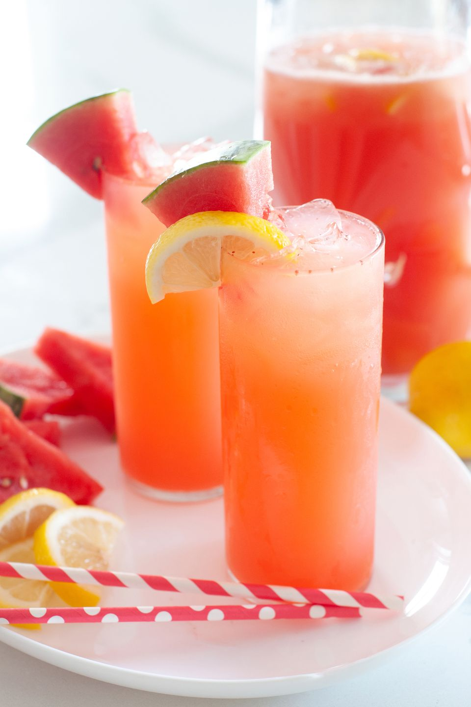 100% whole lemon lemonade with watermelon served in tall glasses and garnished with lemon slices.
