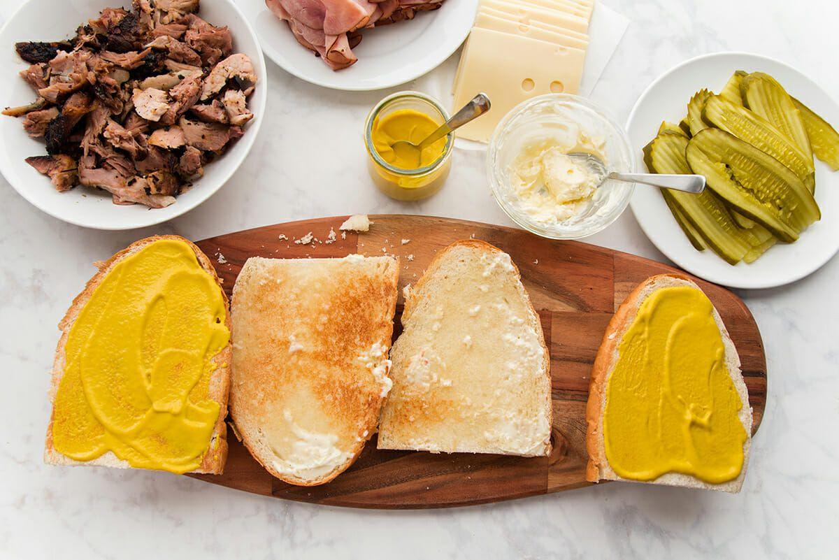 Toasted french bread is cut into quarters and set on a wooden cutting board. The middle pieces are spread with mayonnaise and the outer quarters are spread with yellow mustard. Bowls of shredded pork, sliced ham, yellow mustard, sliced cheese, mayonnaise and sliced pickles are set above.