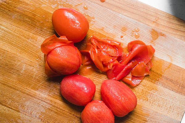 Tomatoes and tomato peel on wood cutting board
