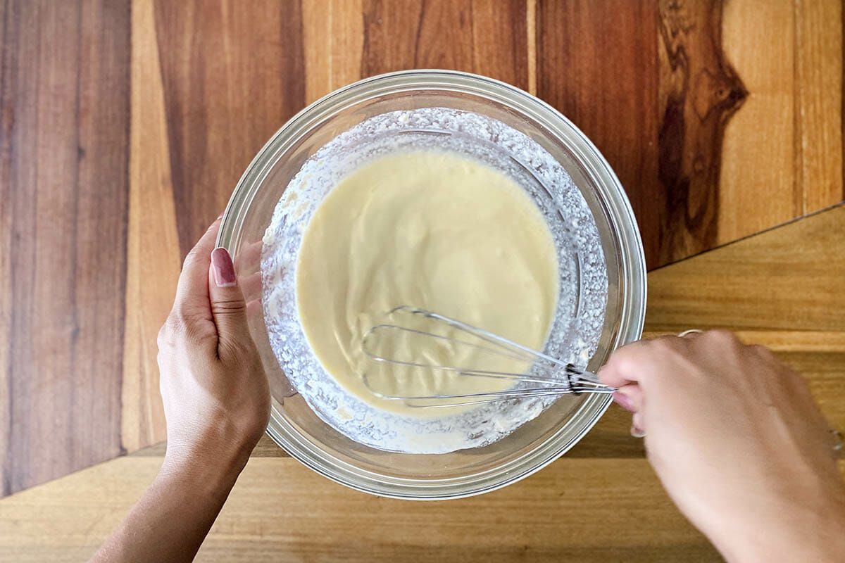 Whisking ingredients to show how to make gluten free cinnamon rolls.