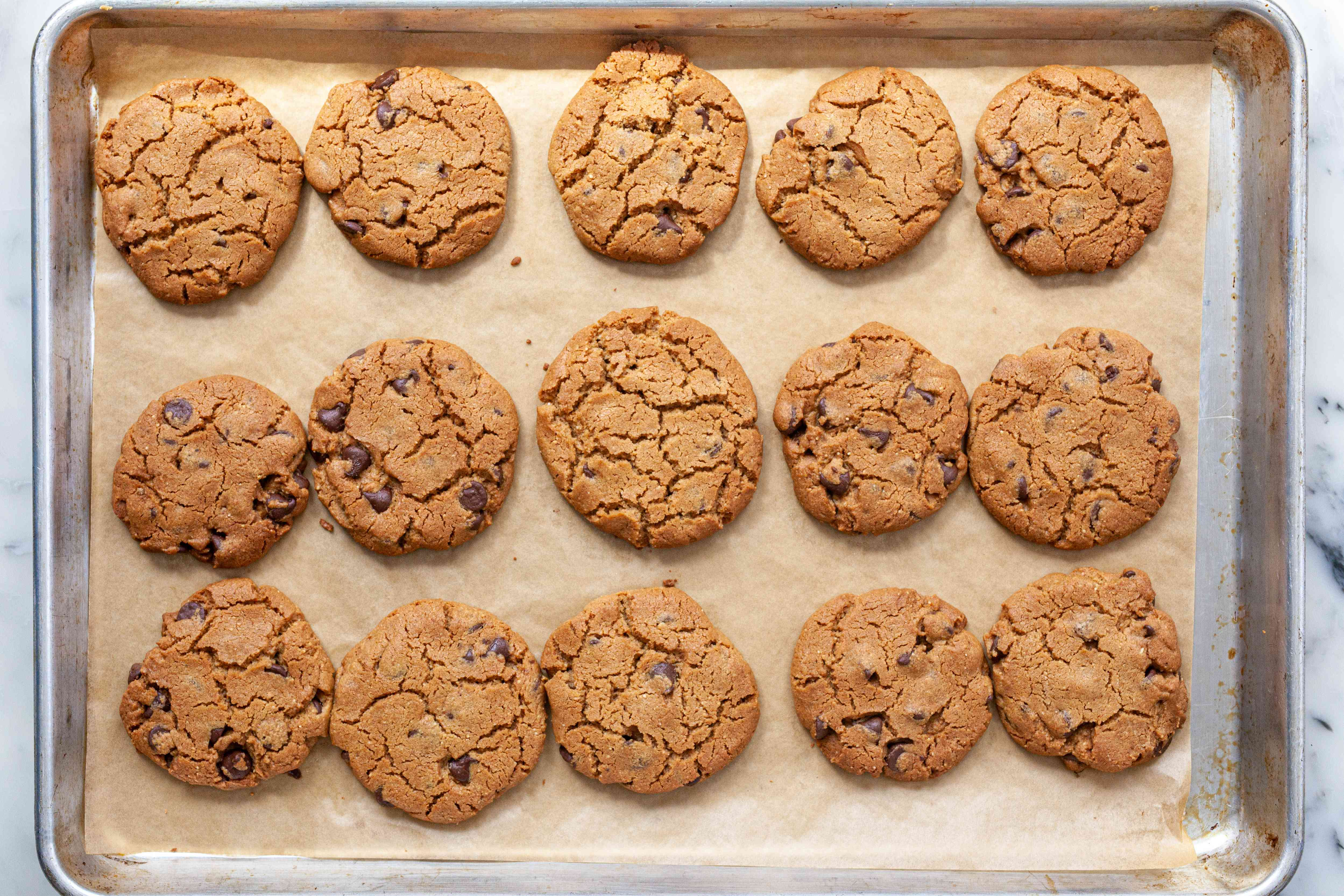 An overhead view of a baking sheet of baked Flourless Peanut Butter Cookies with Chocolate Chips.